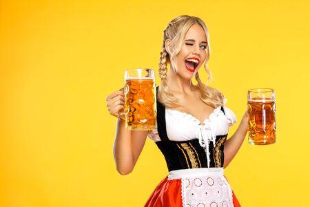Junge Oktoberfest-Kellnerin, die ein traditionelles bayerisches oder deutsches Dirndl trägt und große Bierkrüge mit Getränk auf gelbem Hintergrund serviert. Frau, die auf das Schauen nach links zeigt.