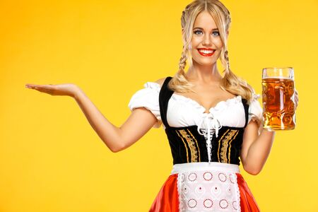 Junge Oktoberfest-Kellnerin, die ein traditionelles bayerisches oder deutsches Dirndl trägt und großen Bierkrug mit Getränk auf gelbem Hintergrund serviert. Frau, die auf das Schauen nach links zeigt.