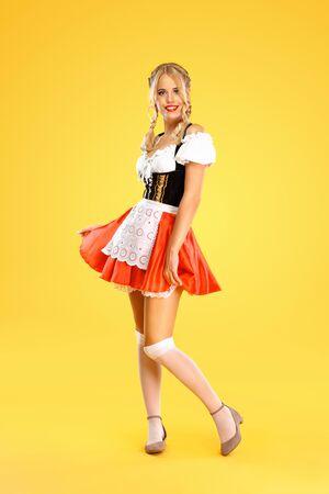 Junge Oktoberfest-Kellnerin, trägt ein traditionelles bayerisches oder deutsches Dirndl isoliert auf gelbem Hintergrund. Foto in voller Höhe.