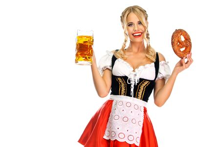 Lächelnde junge Oktoberfest-Kellnerin, die ein traditionelles bayerisches oder deutsches Dirndl trägt und große Bierkrüge mit Getränk und Brezel serviert, isoliert auf weißem Hintergrund.