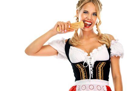 Junge Oktoberfest-Kellnerin, trägt ein traditionelles bayerisches oder deutsches Dirndl mit französischem Hot Dog isoliert auf weißem Hintergrund. Wow-Emotion. Standard-Bild