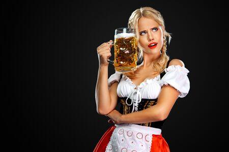 Sexy Oktoberfestmädchenkellnerin, die ein traditionelles bayerisches oder deutsches Dirndl trägt und großen Bierkrug mit Getränk auf schwarzem Hintergrund serviert.