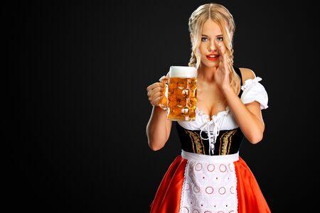 Sexy Oktoberfestmädchenkellnerin, die ein traditionelles bayerisches oder deutsches Dirndl trägt und großen Bierkrug mit Getränk auf schwarzem Hintergrund serviert. Frau hat ein Geheimnis.