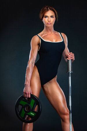 Young fitness woman athlete and bodybuilder with barbell. Individual sports. Sports recreation.