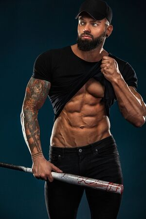 Strong and fit man bodybuilder with baseball bat shows abdominal muscles under a t-shirt. Sporty muscular guy athlete. Sport and fitness concept. Mens fashion. Standard-Bild