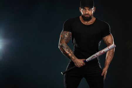 Strong and fit man bodybuilder with baseball bat in black t-shirt. Sporty muscular guy athlete. Sport and fitness concept. Mens fashion.