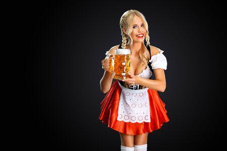 Smiling young oktoberfest girl waitress, wearing a traditional Bavarian or german dirndl, serving big beer mug with drink isolated on black background. Standard-Bild