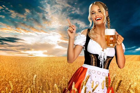 Smiling sexy Oktoberfest girl waitress, wearing a traditional Bavarian dirndl, serving big beer mug with drink outdoor. Woman pointing to looking left. Zdjęcie Seryjne