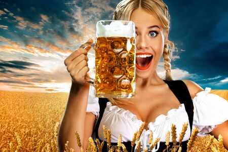 Smiling young sexy Oktoberfest girl waitress, wearing a traditional Bavarian dirndl, serving big beer mug with drink outdoor.