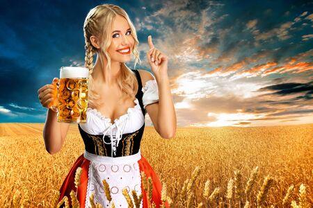 Lächelnde junge Oktoberfestmädchenkellnerin, die ein traditionelles bayerisches Dirndl trägt und großen Bierkrug mit Getränk im Freien serviert. Frau, die auf das Nachschlagen zeigt.