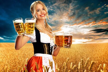 Young sexy oktoberfest girl waitress, wearing a traditional Bavarian dirndl, serving two big beer mugs with drink outdoor.