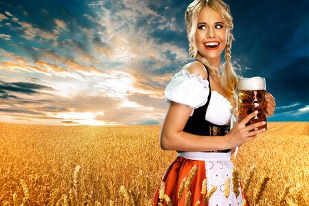 Smiling young sexy oktoberfest girl waitress, wearing a traditional Bavarian or dirndl, serving big beer mug with drink outdoor. Woman pointing to looking left. Banco de Imagens