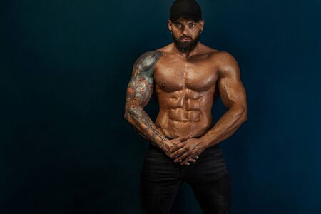 Strong and fit man bodybuilder. Sporty muscular guy athlete. Sport and fitness concept. Mens fashion. Фото со стока