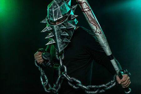 Mysterious man in a helmet with a bat and chains in black wear. Fantasy book or computer game cover concept on halloween disco party. Stockfoto - 131946292