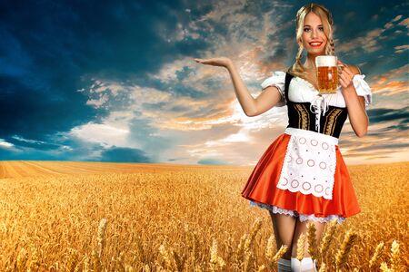 Lächelnde Oktoberfest-Kellnerin, die ein traditionelles bayerisches Dirndl trägt und zwei große Bierkrüge mit Getränk im Freien serviert.