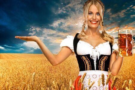 Junge Oktoberfest-Kellnerin, die ein traditionelles bayerisches Dirndl trägt und großen Bierkrug mit Getränk im Freien serviert. Frau, die auf das Schauen nach links zeigt.