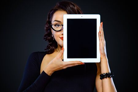Black friday and cyber monday sale concept for shop. Closeup portrait of woman with tablet isolated on dark background. Successful businesswoman in glasses. Stock Photo