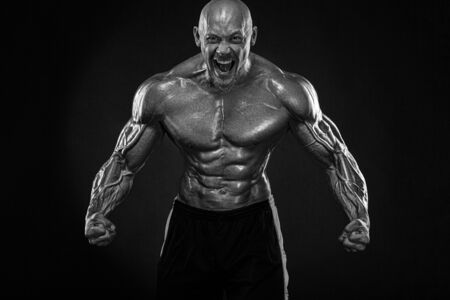 Bodybuilding competitions on the scene. Handsome and fit man sportsmen bodybuilder physique and athlete. Mens fitness motivation. Black and white photo.
