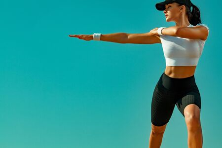 Sporty and fit young woman athlete doing yoga training on the sky background. The concept of a healthy lifestyle and sport. Individual sports recreation.