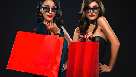 Black Friday sale concept for shops. Two woman in sunglasses holding red bag isolated on dark background at shopping mall.