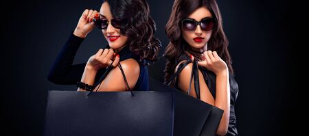 Two women holding grey bag isolated on dark background in black friday holiday at shopping mall.