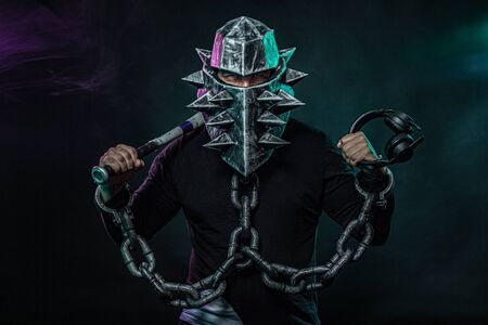 Mysterious man in a helmet with a bat and chains in black wear. Fantasy book or computer game cover concept on halloween disco party. Stockfoto