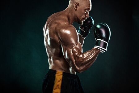 Sportsman, man boxer fighting in gloves on black background. Fitness and boxing concept. Individual sports recreation.
