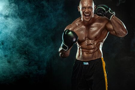 Sportsman, man boxer fighting in gloves on black background. Fitness and boxing concept. Action shoot. Individual sports recreation. 版權商用圖片