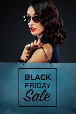 Retrato de detalle del concepto de venta de viernes negro para tienda. Mujer con gafas de sol con bolso grande aislado sobre fondo oscuro en las compras. Foto de archivo