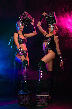 Two beautiful go-go dancer girls in freak costumes on disco in color smoke. Night show women on Halloween party. Stock Photo