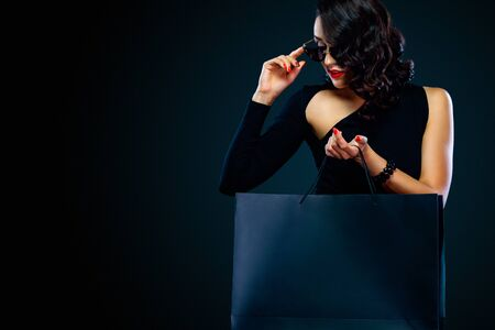 Black Friday sale concept for shop. Happy smiling girl in sunglasses holding big bag isolated on dark background at shopping. Фото со стока