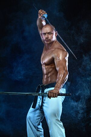 Shirtless man samurai with Japanese sword. Karate fighter on black background with smoke. Handsome and fit man sportsmen bodybuilder physique and athlete. Mens sport motivation. 版權商用圖片