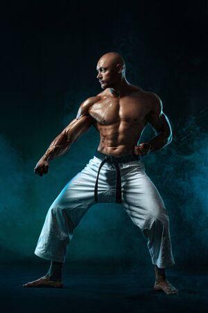 Shirtless man. Karate fighter on black background with smoke. Handsome and fit man sportsmen bodybuilder physique and athlete. Mens sport motivation.
