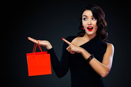 Black friday sale concept for shop. Shopping girl holding red bag isolated on dark background. Woman pointing to looking left on copy space. Reklamní fotografie