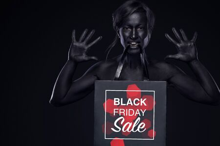 Black friday sale concept for shop. Shopping woman with bodyart and face art holding bag isolated on dark background in holiday.