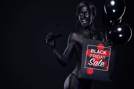 Black friday sale concept for shop. Shopping woman with bodyart and face art holding bag and balloons isolated on dark background in holiday. 스톡 콘텐츠