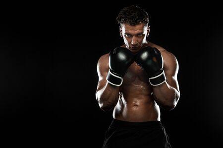 Boxer, uomo che combatte o posa in guanti su sfondo nero. Fitness e concetto di boxe. Ricreazione sportiva individuale.