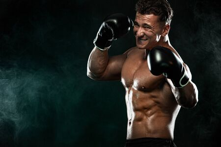 Boxer, man fighting or posing in gloves on black background. Fitness and boxing concept. Individual sports recreation. 版權商用圖片