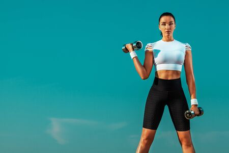 Sporty and fit young woman athlete doing training with dumbbells on the sky background. The concept of a healthy lifestyle and sport. Individual sports recreation.