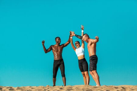 Group of three sportsmens women and men, fit athletes runners after training on sky background. Healthy lifestyle and sport. Friends in black and white sportswear on workout exercise. Fitness concept.
