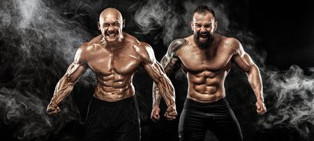 Sport and fitness concept. Two wild sportsmen boxers and bodybuilders posing on black background with smoke before competition or fight. Copy Space. Imagens - 134005508