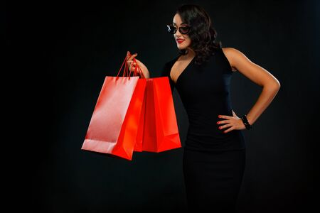 Black Friday sale concept for shops. Shopping woman in sunglasses holding red bag isolated on dark background. Imagens - 134005514
