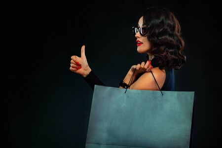 Black Friday sale concept for shop. Girl in sunglasses holding big bag isolated on dark background at shopping. Woman pointing to looking on copy space for sales text. Imagens - 134005516