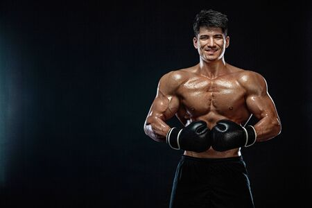 Concepto de fitness y boxeo. Boxeador, hombre peleando o posando con guantes sobre fondo negro. Recreación deportiva individual.