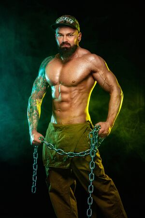 Gay streptizer with naked torso. Muscular fitness sports man, atlete with chains in fitness gym. Energy and power.