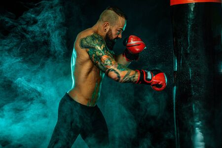 Boxer fighting in gloves with boxing punching bag. Sportsman with tattoos, man Isolated on black background with smoke. Copy Space. Imagens