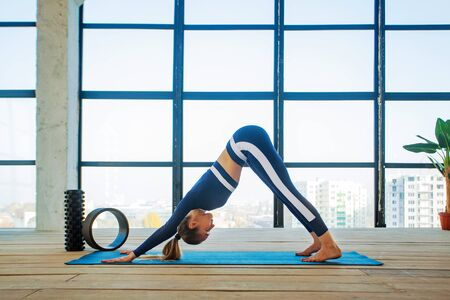 Yoga asana Indoor before a large panoramic window. Sports recreation. Beautiful young woman in yoga pose. Individual sports. Imagens