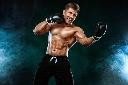 Fitness and boxing concept. Boxer, man fighting or posing in gloves on dark background. Individual sports recreation.