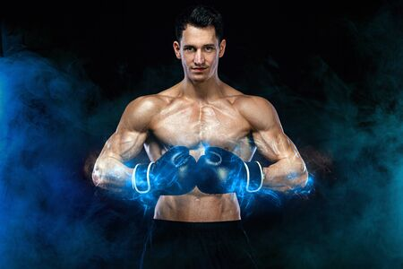 Boxing and fitness concept. Boxer man fighting or posing in gloves on black background. Individual sports recreation. Energy and power.