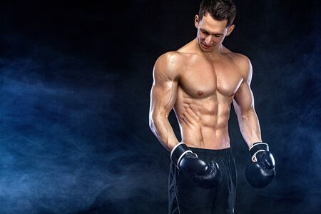 Fitness and boxing concept. Boxer, man fighting or posing in gloves on black background. Individual sports recreation.